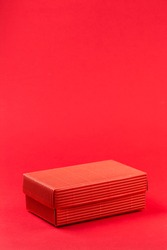 Monochromatic photo of red closed corrugated cardboard box on red background. Valentine's Day gift packaging concept