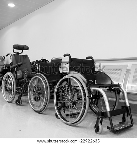 monochromatic photo of wheel chairs parked in a hospital corridor