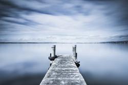 Monochrome abstract landscape. Wooden pier on Lake Zug in Switzerland. Long exposure.