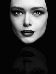 monochrome art fashion portrait of beautiful woman face like a mask. female mask isolate on black.beauty model