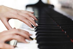 Monochrome black and white manicure nails on piano keys, female graceful hands playing music close up