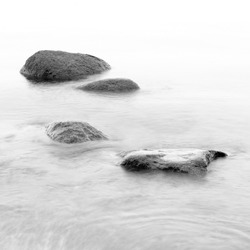 Monochrome black & white shore sea water and stones on the Orlowo beach in Gdynia, Tricity, Poland