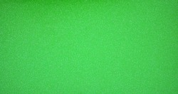 Monochrome bright green surface with a scattering of small silvery shiny blotches. Background, pattern, texture.
