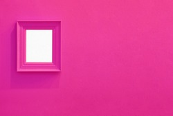 Monochrome concrete wall in pink color with pink painted picture frame. One colored horizontal background with copy space.