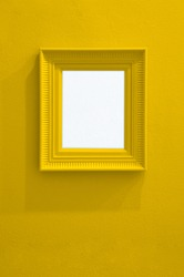 Monochrome concrete wall in yellow color with yellow painted picture frame. One colored background with copy space.