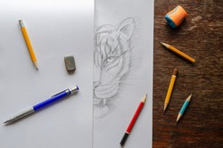 Monochrome Drawing of a tiger made by a pencil on a white sheet of paper. Half of the drawing is covered with a blank sheet of paper. Drawing training, creativity. Top view at an angle.