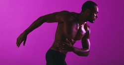 Monochrome fitness portrait of fit athlete. Bare chested man in fitness wear working out on purple background.