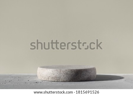 Monochrome gray template for mockup, banner. Flat round granite pedestal on textured background. Stone stand for natural design concept. Horizontal image, center composition, hard light, front view Stockfoto ©