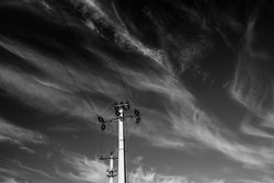 Monochrome image, electricity pylon against dark  sky with white clouds, space for text.