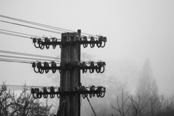 Monochrome image of concrete pole with old broken telegraph and telephon wired line with misty background