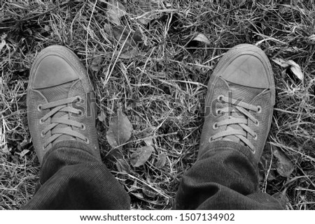 Monochrome image of legs in old sneakers. Old sneakers in the nature.