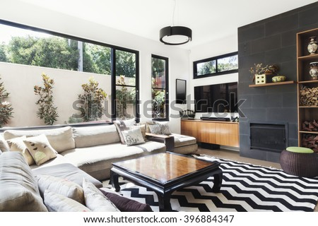 Monochrome living room with wood and grey tiling accents and chevron pattern rug #396884347