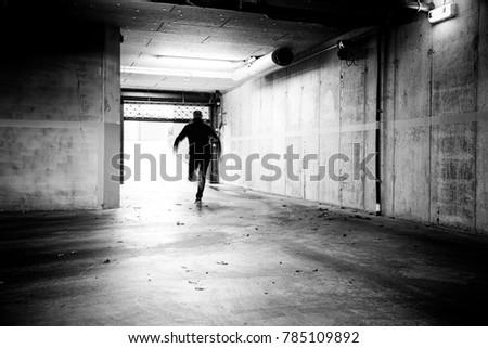 Monochrome of a man fleeing a grungy underground parking.  Stockfoto ©