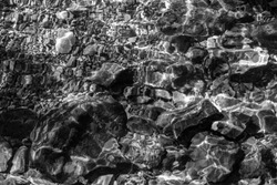Monochrome of stones and pebbles under water in the river. Background and texture of shiny pebbles on the river bottom at tropical forest.