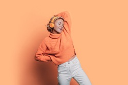 Monochrome photo of a caucasian woman listening to music on headphones posing on a orange studio wall