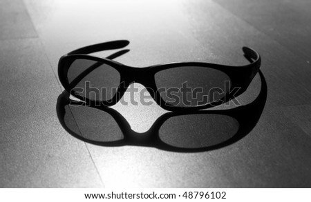 Monochrome photo of black modern sun glasses with back sun light and shadow