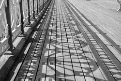 Monochrome photo of old Victorian pier and promenade. The sunlight streams through the intricate designs and creates shadow patterns on the wooden boardwalk