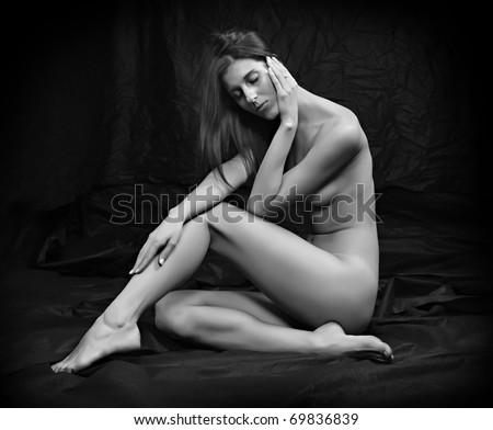 Monochrome photography of sad woman sitting on black background. - stock photo