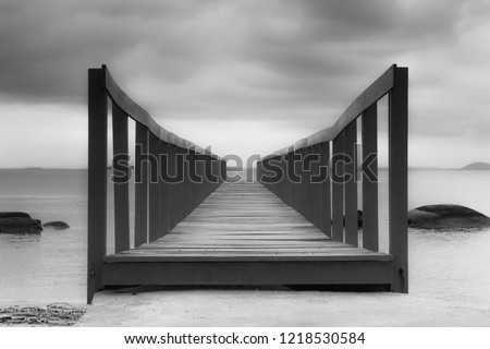 Monochrome picture of an old bridge for fishing boats on Paqueta Island, Rio de Janeiro, Brazil, over Guanabara Bay. Gray sky and calm waters with some rocks. 2017