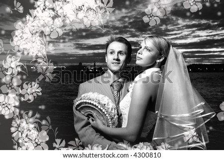 Monochrome picture of bride and groom standing together near the river