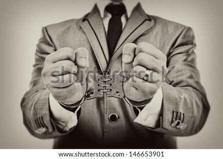 Monochrome portrait of a businessman's hands with handcuffs