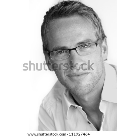 Monochrome portrait of a good looking young businessman in stylish eyeglasses