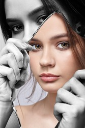 Monochrome portrait of girl with a shard of the mirror. Female with mirror shard in hand posing on gray background. Color face reflection in mirror splinter.