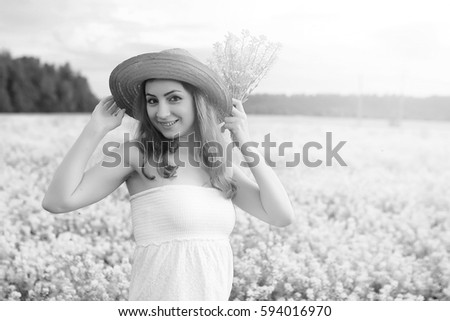 monochrome portrait of young girl in a hat standing in huge field of flowers #594016970