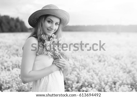 monochrome portrait of young girl in a hat standing in huge field of flowers