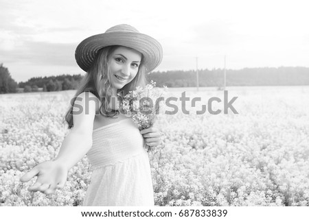 monochrome portrait of young girl in a hat standing in huge field of flowers #687833839