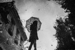 Monochrome puddle reflection silhouette of girl with umbrella near strange house