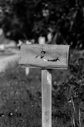 Monochrome rusty, damaged rural mailbox  in front of trees in the summer.
