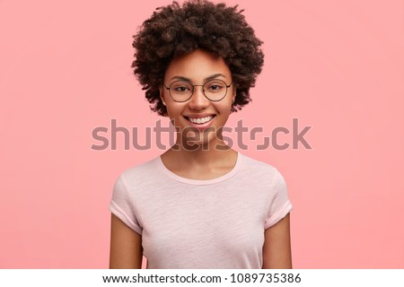 Monochrome shot of happy African American businesswoman with positive smile, has crisp dark hair, rejoices having weekend and good rest after hard working exhausting week, isolated on pink wall