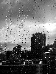 Monochrome shot of raindrops on the glass against the city background. The sun after the rain