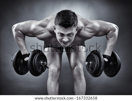 Monochrome shot of young athletic man working with heavy dumbbells