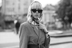 Monochrome street fashion portrait of elegant woman wearing trendy headscarf, black cat eye sunglasses, wicker belt, houndstooth blazer, posing in street of European city
