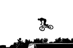 Monochrome summertime shot of man's silhouette on bicycle performing various dangerous tricks or stunts in skate park. Unrecognizable rider jumping high against blank copyspace sky background