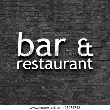 Monochrome version of Bar & restaurant sign set on a very old brick wall