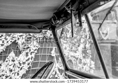 Monochrome view of a well-known left-hand drive World War Two military vehicle showing part of the steering and canvas top. The background shows part of an army field hospital.