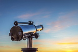 Monocular telescope at sunset with a cloudy sky