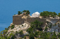 Monolithos medieval fortress and church on a mountain cliff against the backdrop of the magnificent Aegean Sea (Rhodes, Greece)