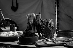 Monotone image of freshly baked scones in a wooden bowl on a table beside replica viking objects at a re-enactment country fair
