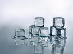 Monotone image of melting ice cubes. The ice cubes are randomly stacked and lit from behind on the right. There is a reflection of the cubes and the image darkens lower left. Copy space at top.