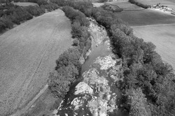 Monotone of a drone aerial of a country creek lined with boulders and bordered by trees