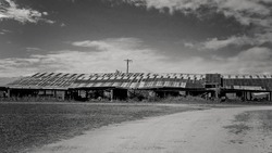 Monotone of a long low decrepit old shed with rusted iron roof against a dramatic sky background