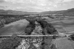 Monotone of bridge over a rocky creek amongst a patchwork of fields of sugarcane and a mountain background.