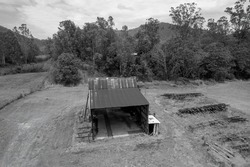 Monotone of historical iron maintenance sugar mill shed in a park landscape with stacked old railway tracks to the side