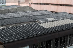 Monotone roof made of metal material as galvanized iron roof in Bangkok. Industrial exterior design as modern wallpaper. Durable roof view from next building.