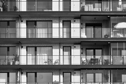 Monotonous balconies and terraces with tables and chairs in a big boring apartment building with big windows, black and white