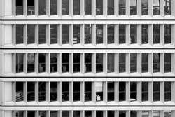 Monotonous facade of office tower with large window front in concrete construction, black and white
